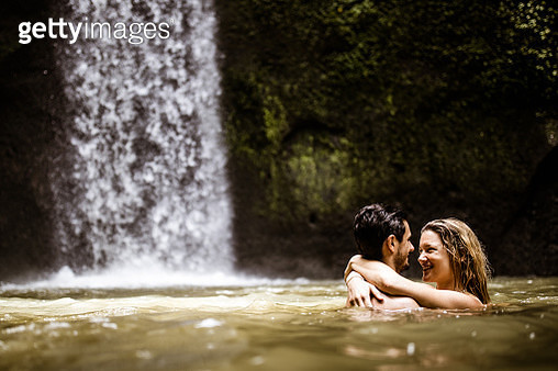 Happy couple in love communicating while enjoying in water at rainforest. - gettyimageskorea