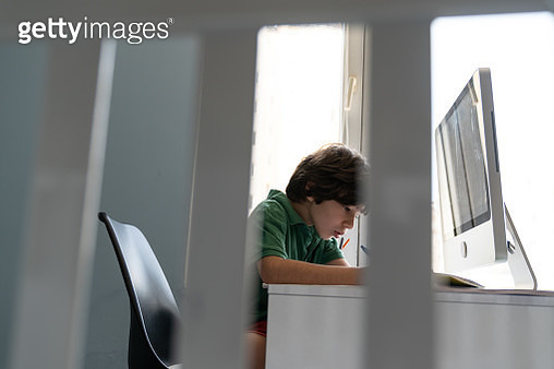 Schoolboy Homeschooling Online At Home Seen Through Cradle Fence - gettyimageskorea