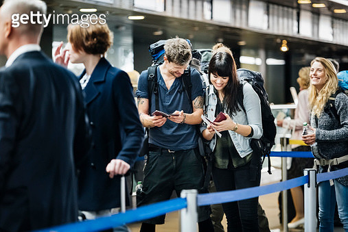 Young backpacker couple waiting at check in counter at the airport - gettyimageskorea