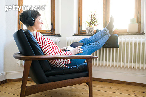 Short-haired woman with headphones relaxing in lounge chair in stylish apartment - gettyimageskorea