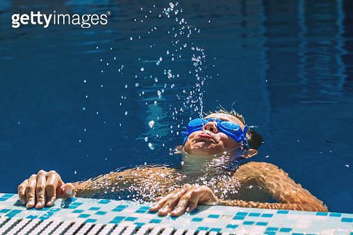 Happy little boy swimming in the pool - gettyimageskorea