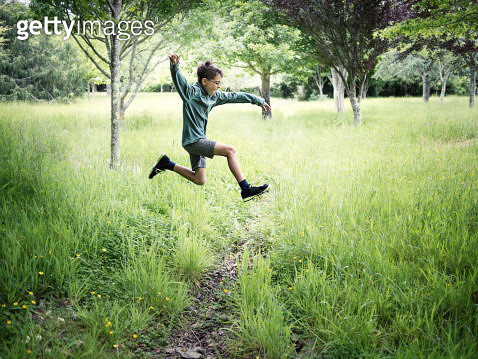 Boy takes running jump across ditch in meadow. - gettyimageskorea