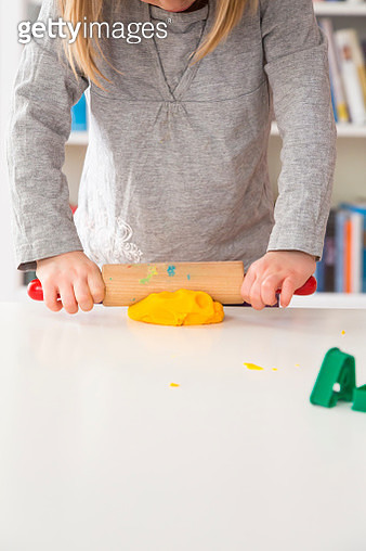 Little girl rolling out yellow modeling clay - gettyimageskorea