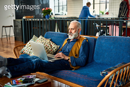 Senior man with trendy moustache working on laptop at home - gettyimageskorea