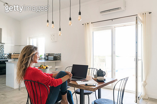 Woman using laptop on dining table in modern home - gettyimageskorea