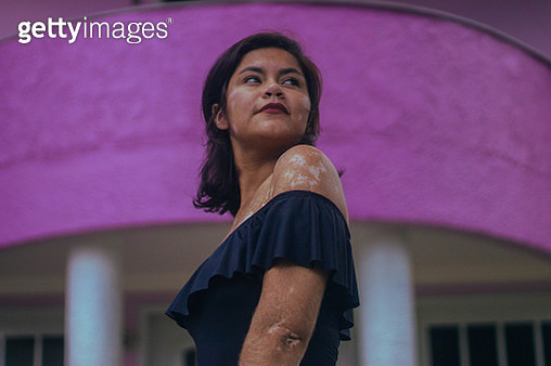 Woman posing next to a purple house - gettyimageskorea