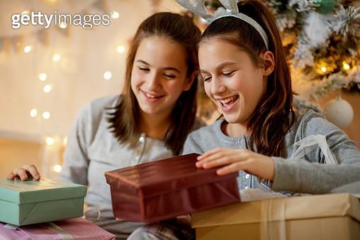 Cheerful teenage girls in pajamas opening Christmas gifts - gettyimageskorea
