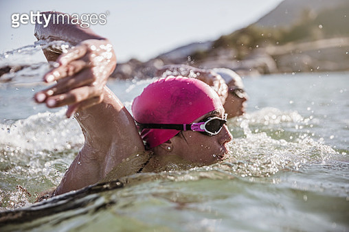 Determined female open water swimmer swimming in sunny ocean - gettyimageskorea