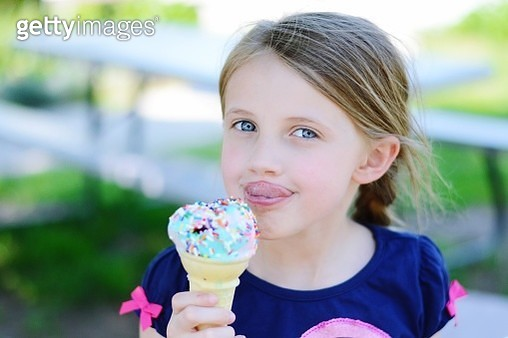 Portrait Of Cute Girl Sticking Out Tongue While Holding Ice Cream - gettyimageskorea