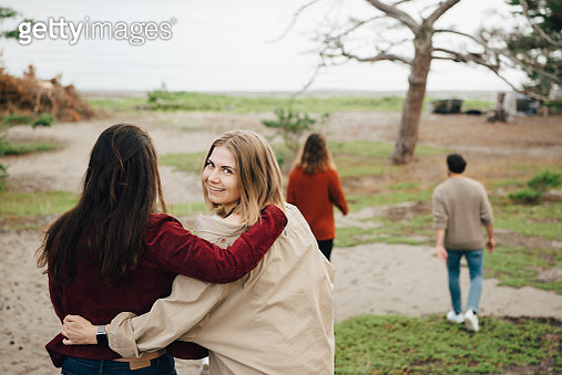 Portrait of smiling woman walking with friend outdoors during vacation - gettyimageskorea