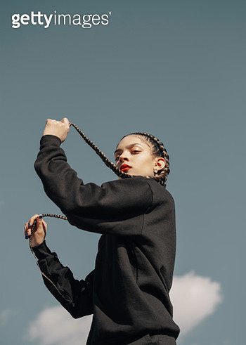 Young hispanic woman with long braids dancing and playing with her hair photographed against the blue sky. - gettyimageskorea