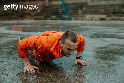 Close up of a strong man who is doing push ups on a rainy day - gettyimageskorea