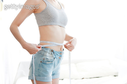 Woman measuring waist, mid section - gettyimageskorea