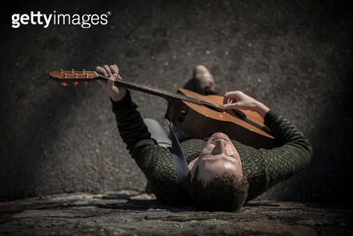 Musician Man Playing on his Guitar and Leaning Against a Stone Wall with Sunlight - gettyimageskorea