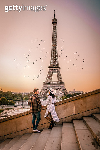 Full Length Of Couple Standing Against Eiffel Tower On Steps In City During Sunset - gettyimageskorea