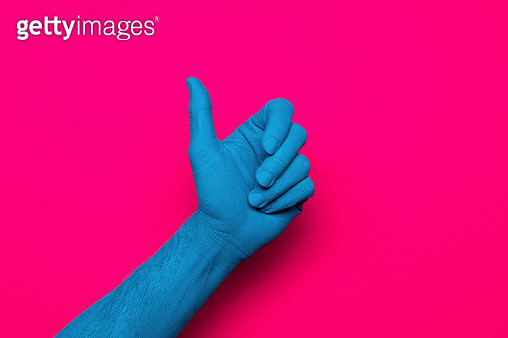 Close-up of blue painted hand gesturing thumb up against pink background - gettyimageskorea