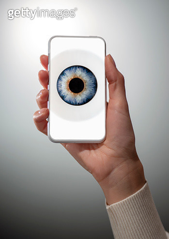 Woman's hand holding cell phone with eye on screen - gettyimageskorea