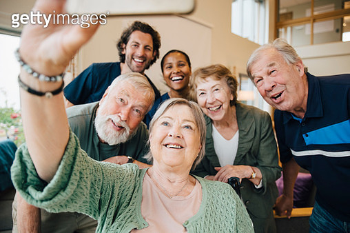 Senior woman taking selfie with friends and healthcare workers at retirement home - gettyimageskorea