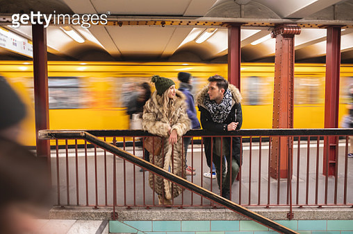 Young couple waiting for their train and chatting - gettyimageskorea