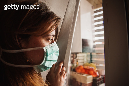 Young woman in quarantine wearing a mask and looking through the window - gettyimageskorea