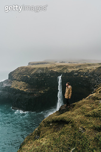 Man looking at scenic  view of Múlafossur waterfall falling into the sea in Faroe Islands - gettyimageskorea
