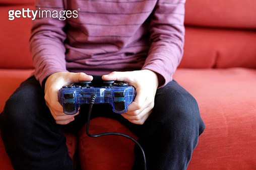Close-up of boy playing video game at home - gettyimageskorea