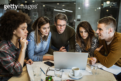 Mid adult manager and his team cooperating while working on computer in the office. - gettyimageskorea