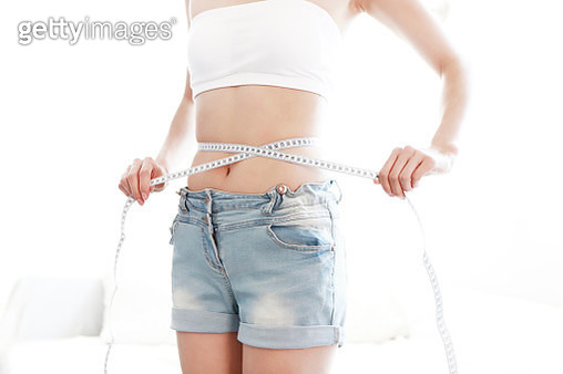 Woman Measuring Waist With Tape Measure - gettyimageskorea