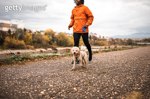 Young Brazilian running with dog during autumn morning - gettyimageskorea