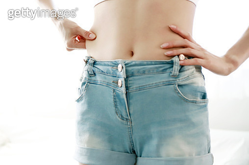 Woman pinching waist, mid section, close-up - gettyimageskorea