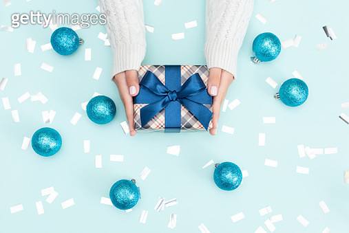 Flat lay of woman hands holding gift wrapped and decorated with bow on blue background with copy space. - gettyimageskorea