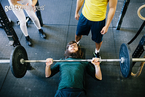 A man lifting weights on a bench while being supported by his friends at the gym. - gettyimageskorea