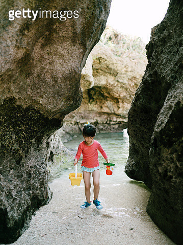 Little girl playing on beach in cave, Okinawa, Japan - gettyimageskorea
