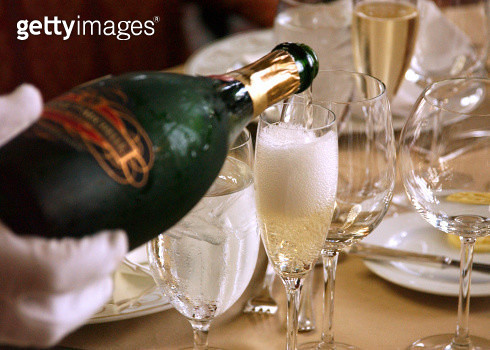 Bottle of champagne being poured into a flute by waitstaff with white gloves. - gettyimageskorea