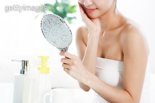 Young woman looking at skin in mirror - gettyimageskorea