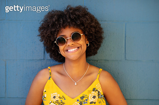 Beautiful young woman standing against blue wall - gettyimageskorea