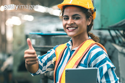 Portrait Of Smiling Woman Wearing Hardhat Gesturing While Holding Digital Tablet In Factory - gettyimageskorea