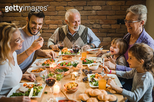 Happy multi-generation family communicating while enjoying in dinner at dining table. - gettyimageskorea