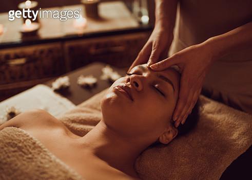Serene African American woman receiving head massage at beauty spa. - gettyimageskorea