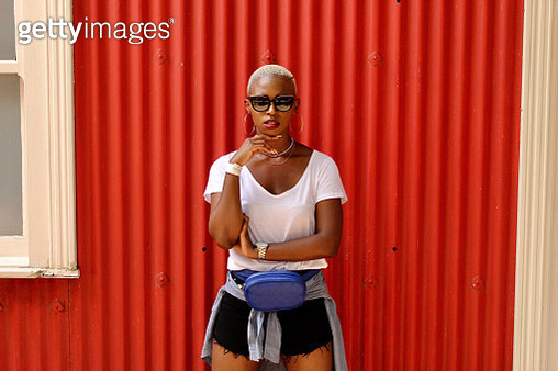 Young women from South Africa standing in front of a red wall. She is wearing sunglasses. - gettyimageskorea