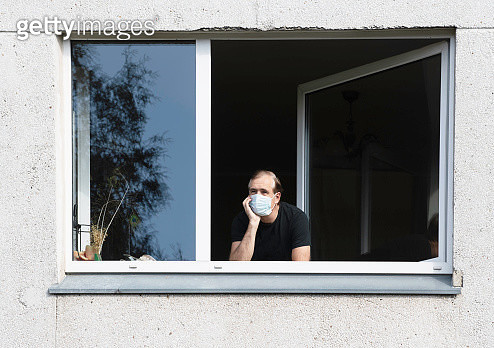 Man wearing a face mask looking out of a window, Lithuania - gettyimageskorea